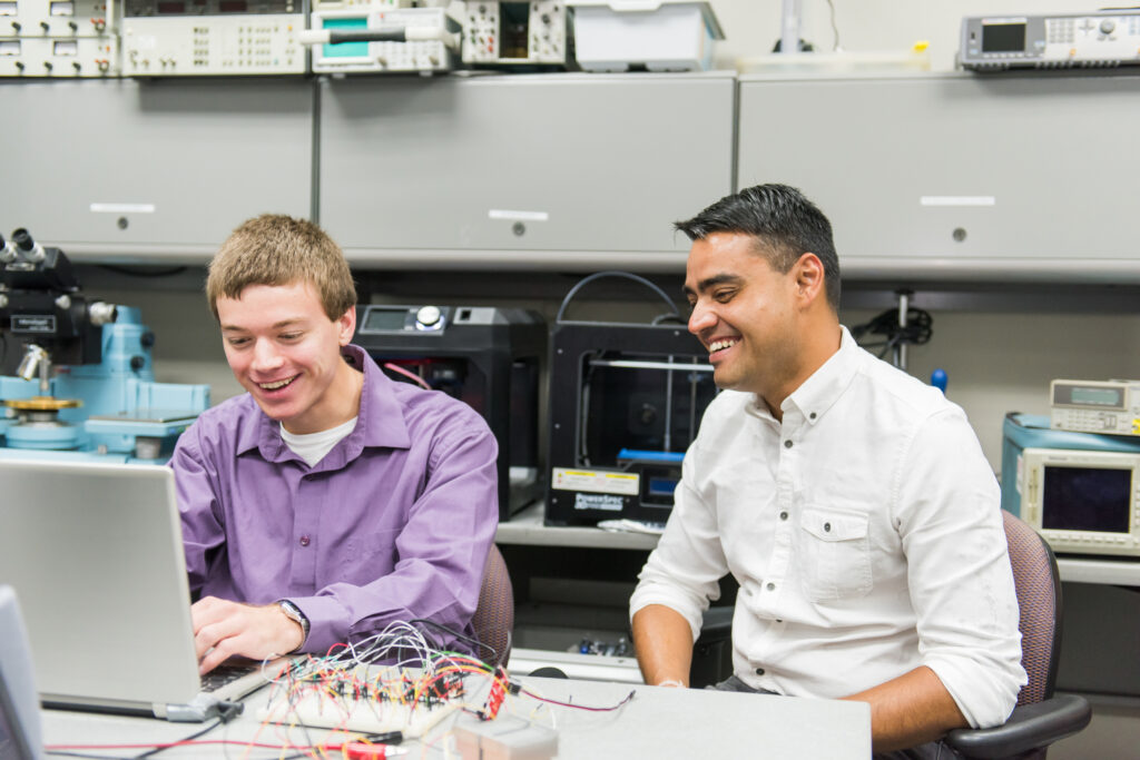 A student and professor work in an engineering lab, seated in front of a computer.