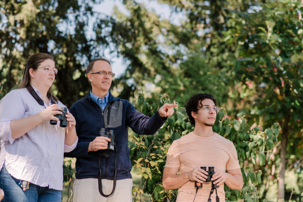 three people outdoors with binoculars