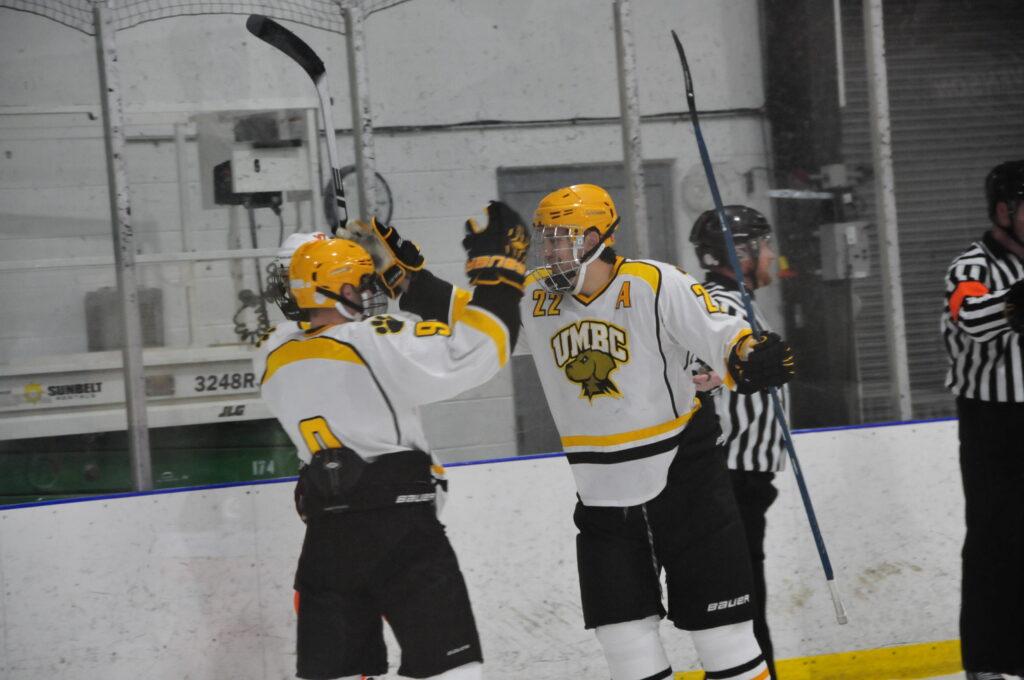 Ryan Atkinson playing hockey with teammate